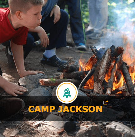 A child blowing on a campfire